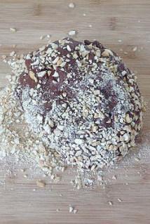 【可可果仁面包卷】,发好的面团取出,放在腰果碎上。