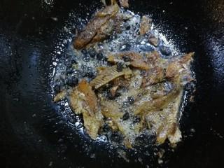 豆豉鲮鱼油麦菜,倒入准备好的豆豉鲮鱼,中火煸炒,用铲子将大块鱼肉铲碎,多炒一会,炒出香味