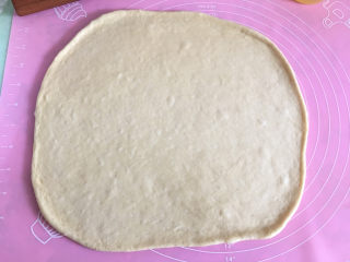大虾披萨,将面团取出擀成和披萨盘大小的圆形。