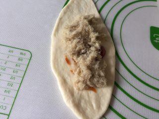 肉松小面包,拿一个面团擀成牛舌状,抹上披萨酱或沙拉酱,上面再铺一层肉松。