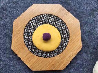 紫薯南瓜椰蓉球,取一小块南瓜面团压扁,放上紫薯馅,南瓜面团由外向内慢慢收口,把紫薯面团包裹在里面,再搓成圆球。