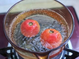 番茄肉酱意面,锅中烧开水,将番茄划十字的部位朝下放入水中烫煮约三十秒