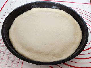 海陆至尊披萨,将擀好的面皮放入披萨盘内,用手按压面皮,把面皮撑至与盘子同样大,边缘挤出一圈圆边,