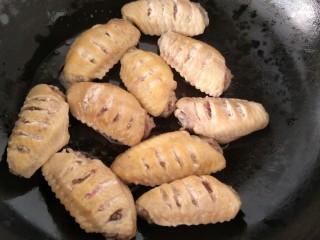 可乐鸡翅,锅里放油加热,放入焯好水的鸡翅煸炒。