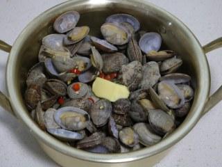 深夜食堂之酒蒸蛤蜊,开盖看蛤蜊开口就好了,加入黄油块,关火盖盖子焖1分钟。