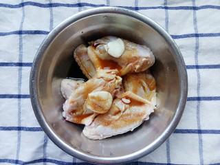 电饭锅+鸡中翅焖饭,鸡中翅先放入两粒蒜头,两勺盐和两勺酱油