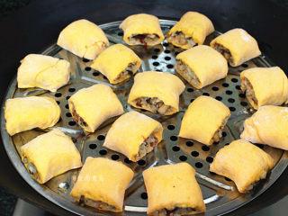 南瓜腊味糯米卷,蒸笼表面涂抹一层食用油,将糯米卷间隔开摆在上面