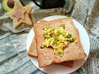 牛油果滑蛋吐司――5分钟快手营养早餐,将炒好的滑蛋牛油果放进吐司刻好的图案中,两片吐司中间再加一片火腿片即可。