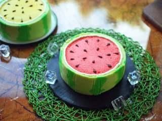 夏季私房热门的西瓜蛋糕,绿色的西瓜皮蛋糕切成合适的高度,围在蛋糕体外侧,稍微往内压一下,粘紧。西瓜皮和红蛋糕分界线之间,挤一圈奶油。最后用黑巧克力在表面挤成西瓜子,完成后放入冰箱冷藏保存。