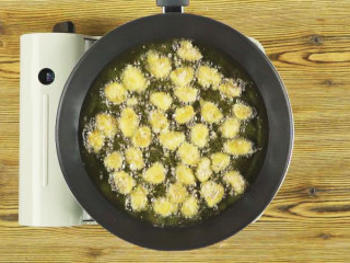 杏鲍菇秒变鸡米花,锅中倒油烧热,放入杏鲍菇,小火炸至色泽金黄,捞出沥油