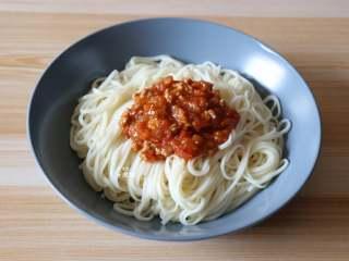 番茄肉酱拌面,再捞出装盘,滴几滴玉米油、撒适量盐、浇上熬煮好的肉酱即可;