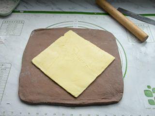 脏脏包,将松弛好的面团取出,在硅胶垫上撒些面粉放粘连,再把面团擀成比黄油片稍大的面片,把黄油片放在中央。