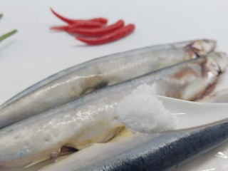 简单美味的麻辣烤秋刀鱼,加盐一勺,均匀地涂抹在鱼身上。