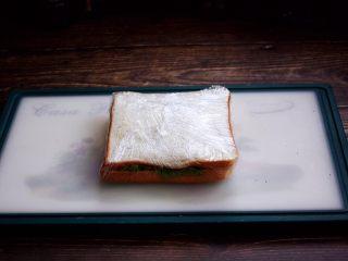 三明治,用保鲜膜包好。 用保鲜膜包裹之前用手将三明治压一压,压的扁些更便于包裹,用保鲜膜包裹时尽量包的紧实些。