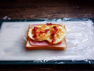 三明治,放入煎好的鸡蛋,挤上少许的番茄沙司。