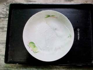 椰蓉南瓜小方,取一只干净盘子,贴上保鲜膜,方便脱模,均匀的撒上一些椰蓉,方便到时候脱模。