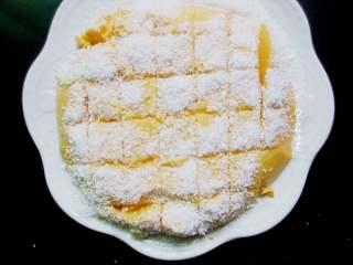椰蓉南瓜小方,晾凉后的南瓜糊盖上保鲜膜,放入冰箱冷藏两小时以上,凝结成块。成型后直接倒扣脱模,分割成小块,再裹上椰蓉即可食用。
