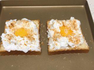 快速早餐吐司片-鸡蛋味,蛋白霜挑入吐司片上,中间留出空间,放入蛋黄,表面撒少许细砂糖,再放一些切吐司片出来的碎隙。