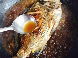 美味家烧+红烧鱼,用汤勺将汤汁淋在鱼身上