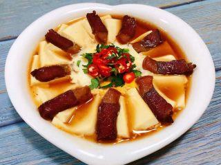 腊肉蒸豆腐卧蛋,调味汁均匀的淋在腊肉豆腐和鸡蛋上面中间撒上香菜和辣椒粒瞬间美极了