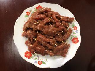 孜然牙签牛肉,用牙签将牛肉一根根串好,放在盘里。