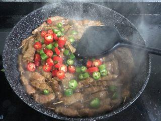 孜然牙签牛肉,所有的肉都已变色,加入青红辣椒和蒜末翻炒均匀。