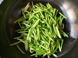 蒜苔炒腊肉,放入蒜苔和腊肉一起煸炒。