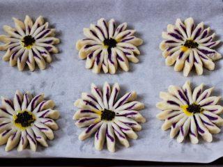 清新脱俗的紫薯菊花酥,将做好的紫薯酥放入烤盘中摆放整齐,紫薯酥中间点一点蛋黄液,撒上一点黑芝麻做装饰。