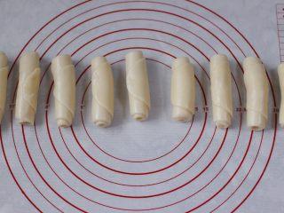 清新脱俗的紫薯菊花酥,从牛舌状面团的一头卷起,一直卷到尾,依次做好所有的面团,盖上保鲜膜松弛15分钟。