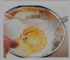 双色可丽饼,事先混合好牛奶、鸡蛋和砂糖,在面粉中间挖一个坑,倒入混合溶液。用打蛋器从中央开始,慢慢向外旋转着搅拌,让面粉一点点溶解,搅拌至材料柔滑,没有大颗粒。