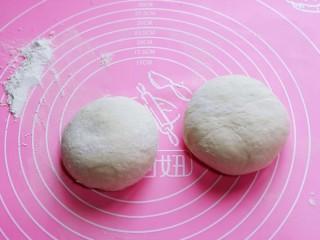 披萨新吃法~奥尔良鸡丁披萨,发酵好的面团取出,分成2份,盖上湿布揉圆醒发10分钟。