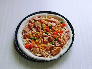 披萨新吃法~奥尔良鸡丁披萨,再把做好的奥尔良鸡肉均匀的铺在披萨皮上面。