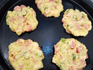 土豆泥火腿鸡蛋饼,把土豆泥做成圆形状,倒入适量油,压扁放入平底锅煎制。