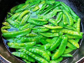 蒜蓉荷兰豆,锅中烧开水放入荷兰豆焯水时间不要过长变色全部漂浮上来即可,可以加一点点食用碱这样荷兰豆颜色更加翠绿
