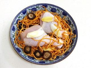 虫草花蒸鸡腿,底下先放些葱段,摆上鸡腿,放上虫草花和泡发好的香菇、姜片。