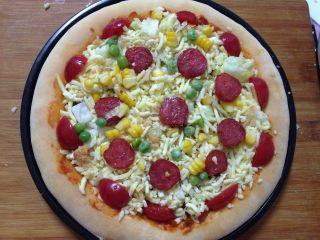 腊肠肉松披萨,最后在表面点缀小番茄、腊肠片、玉米粒、豌豆粒