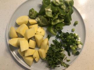 土豆香菇焖鸡,土豆去皮,切成滚刀块;青椒洗净切成不规则小块;小葱、香菜切沫。