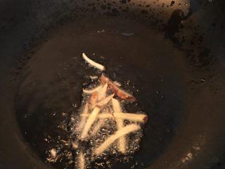 板栗烧鸡翅,热锅倒入些许油,待油烧热后加入姜丝煸炒