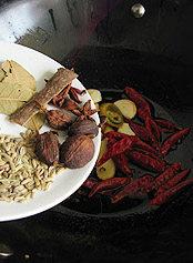 川味红油火锅,继续加入葱、姜、蒜和整粒干红椒、豆豉,再加入所有的香料