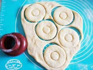 甜甜圈,将发酵好的面团取出,排出气孔,擀成1.5cm厚的面皮,让其松弛五分钟后,用甜甜圈模具在面皮上压出甜甜圈模型,取出中间多余圆孔。 没有甜甜圈模具的,可以用一个大玻璃杯压出大圆形,用小的圆形模具如裱花嘴的圆形。