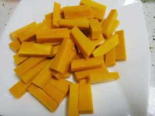 咸蛋黄焗南瓜,南瓜洗净后去皮去瓜瓤,切成小长条,如图。放入一勺盐与南瓜条拌匀,腌制二十分钟左右,让南瓜腌出水份。