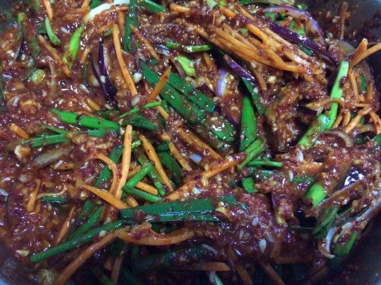 辣白菜,如图接着加入葱段、韭菜、胡萝卜丝、洋葱搅拌均匀