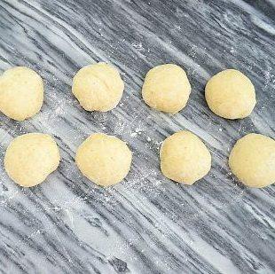 土豆鸡肉芝士包,发酵好的面团取出用手轻压排干净面团里面的气体,分成10份(约38克一份),揉圆,放一边松驰15分钟。