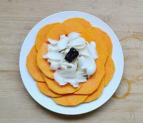 南瓜蒸百合,将南瓜块如图式一样摆两圈,成花形,再将红枣和百合放在中间。