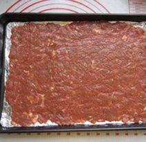 自制猪肉脯,拿下保鲜膜,放到烤盘中。