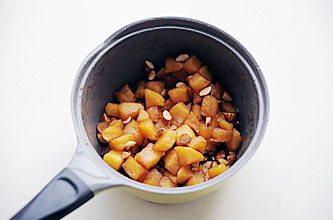 圣诞平安派(苹果派),再次开火加入苹果块,香草荚刮出香草籽与香草荚一同放入锅中,中小火熬煮至汤汁浓稠,苹果变软后关火,加入杏仁和朗姆酒拌匀待用