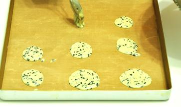 黑白芝麻薄脆,在平烤盘上平铺上油纸,用汤匙挖少许的饼干面粉平铺在烤盘上,中间要留较大的位置以便摊平饼干。