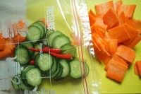 浅渍(日式腌菜),青瓜片轻轻挤干水,和红萝卜片、辣椒一起放进密实袋。