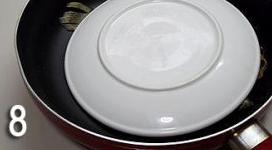 香煎黄花鱼,直至两面都酥脆金黄时,把锅内的油倒掉,用盘子倒扣在鱼上。
