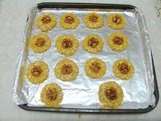 核桃燕麦饼干,取出,分成合适大小的剂子,用手团圆,在手掌按扁,在中心位置涂抹少量焦糖浆,把半个核桃仁粘上,轻轻按牢。